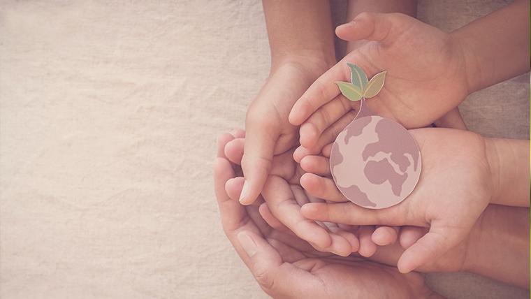 Dłonie dorosłej osoby i dzieci trzymające kartonikową planetę - Dbanie o środowisko – jak możesz pomóc?
