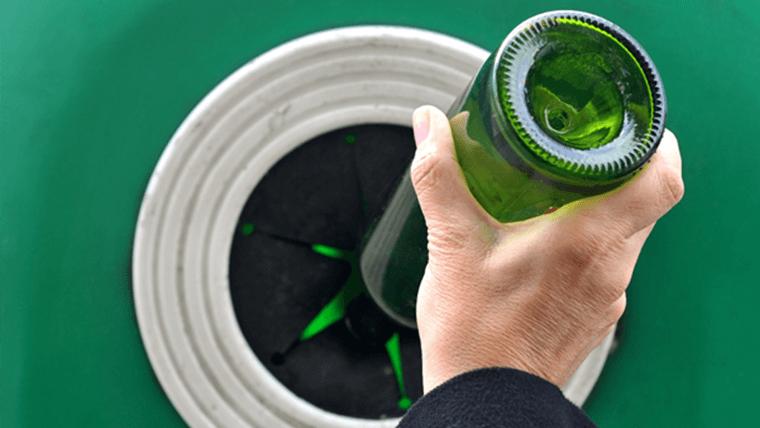 Szklana zielona butelka wrzucana do śmietnika na szkło - Recycling – co to jest?